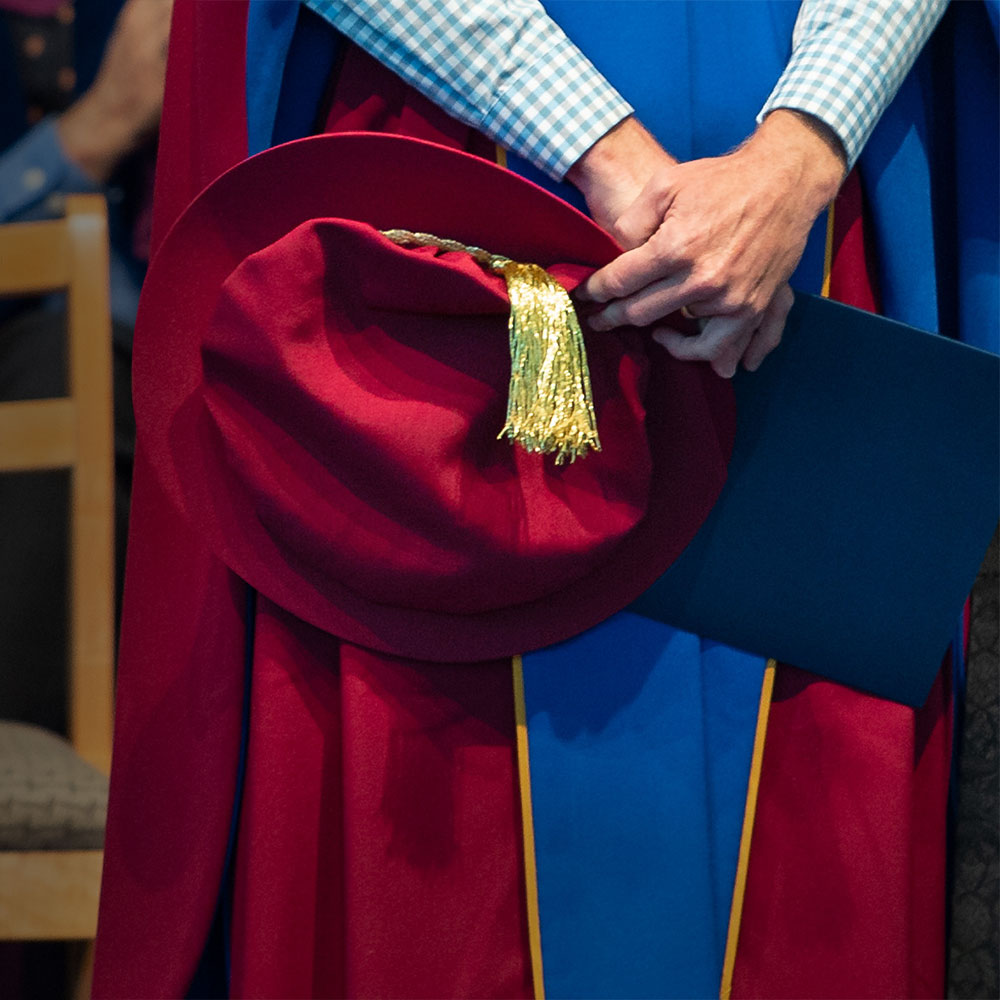 Graduate holding cap and dipoma